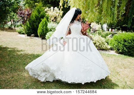 Gorgeous Brunette Bride Posed On Green Garden Courtyard