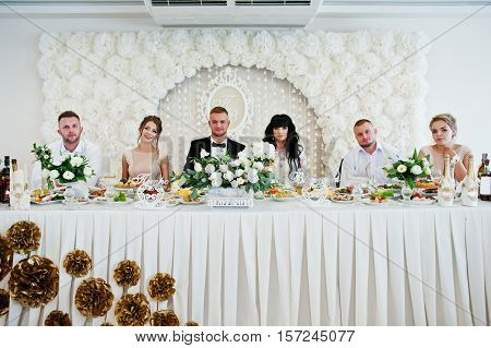 Wedding Couple With Best Man And Bridesmaid Sitting On Table At Restaurant.