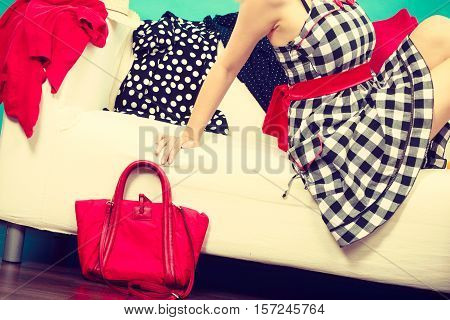 Woman wearing checked dress relaxing on sofa after shopping red bag next to couch clothes all over place.