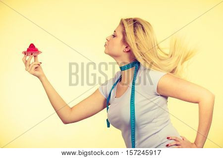 Restrictive diet temptation losing weight concept. Woman holding strawberry sweet cupcake having measure tape around her neck. Studio shot on yellow background
