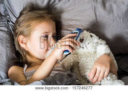 Little Child Girl Measures the Temperature of a Non-Contact Thermometer. Health Care and Illness Concept. Studio Photo