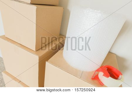 Variety of Packed Moving Boxes with Materials In Empty Room Against Wall.