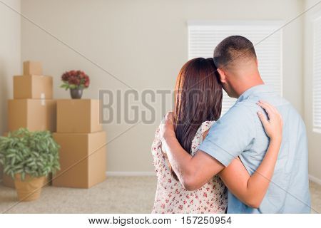Young Military Couple Facing Empty Room with Packed Moving and Potted Plants.