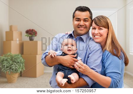 Happy Mixed Race Family with Baby in Room with Packed Moving Boxes.