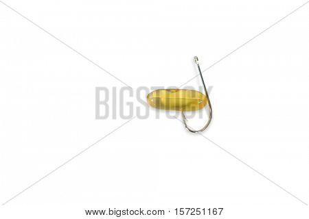 Close-up of capsule and fishing hook against white background