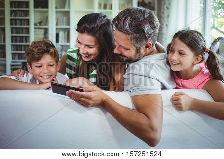 Parents sitting on sofa with their children and using mobile phone in living room at home