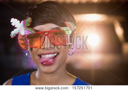 Portrait of woman wearing fancy sunglasses making funny faces in bar