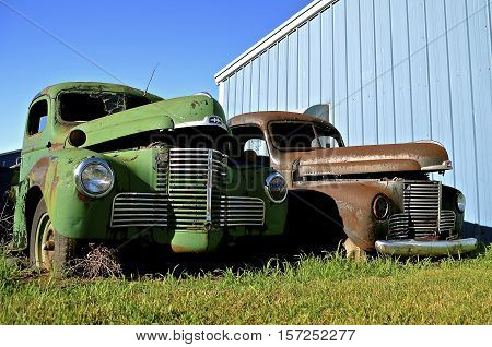 MANDAN, NORTH DAKOTA, July 1, 2016: The old International pickups with partially open hoods  are a product of the International Harvester Company which was a United States manufacturer of agricultural machinery, construction equipment, trucks, and  formed