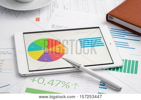 Business analytic with tablet computer, paper and pen financial concept