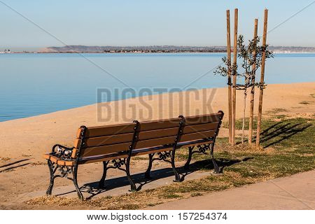 Empty bench at Chula Vista Bayfront park with San Diego bay and Point Loma in the background.