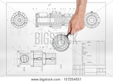 A male hand holding a magnifying glass over a detail drawing. Engineering and design. Technical drawing. Machinery parts.