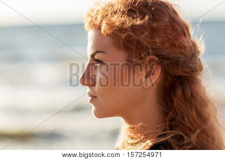 people, facial expression and emotion concept - happy young redhead woman face on beach