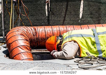 Worker wearing safety gear and looking down manhole in an urban setting.