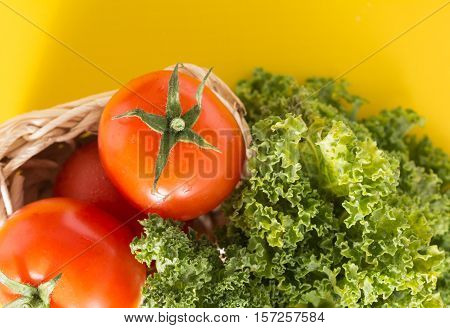 Heap Of Red Cherry Tomatoes And Kale Leaves, On Vivid Yellow Background.