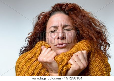 Cold Young Woman Snuggling Into A Winter Top