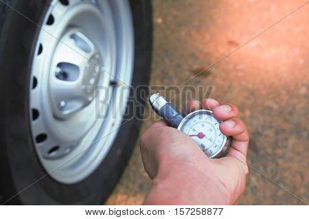 Close up hand checking air into a car tire.