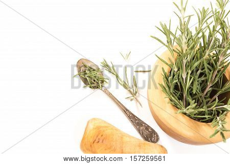 Fresh Rosemary In  Wooden Mortar With Pestle On Withe Background.
