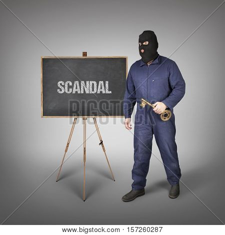 Scandal text on blackboard with thief and key