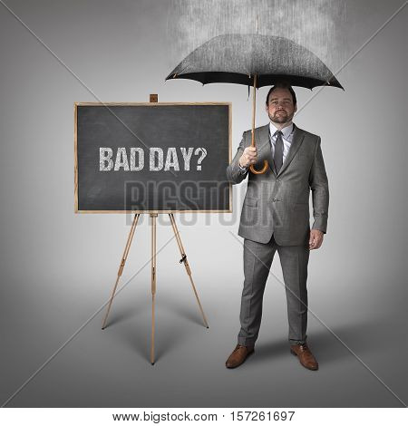 Bad day text on blackboard with businessman and umbrella