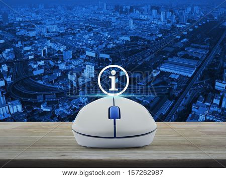 Wireless computer mouse with information sign icon on wooden table over city tower street and expressway