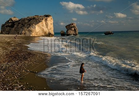 Illuminated with evening sun Aphrodite's Rock (Petra tou Romiou or Rock of the Greek - Cyprus) against beautiful sky. Beach waves and girl in foreground.