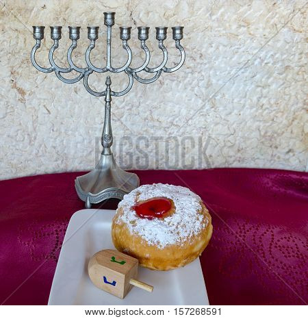 Festive sweet donuts and menorah are traditional symbols of Hanukkah holiday