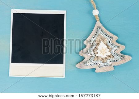 Blue and white christmas with christmas tree and instant photo on blue wooden background, vintage style