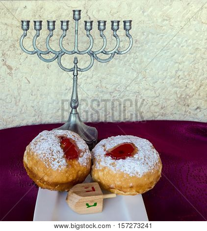 Festive sweet donuts and menorah are traditional symbols of Hanukkah holiday. Selective focus.