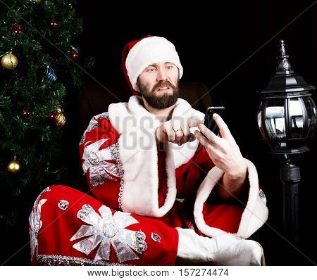 bad brutal Santa Claus holding the bag with gifts and dissatisfied talking on phone on the background of Christmas tree. poster