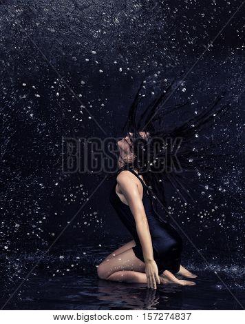 Pretty brunette woman in black dress  under the water drops in aquastudio sitting in water on the knees