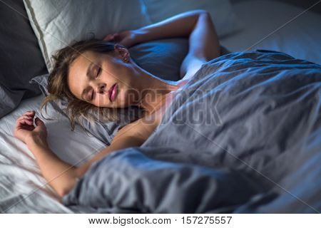 Beautiful young woman sleeping in bed (colour toned image; shallow DOF)