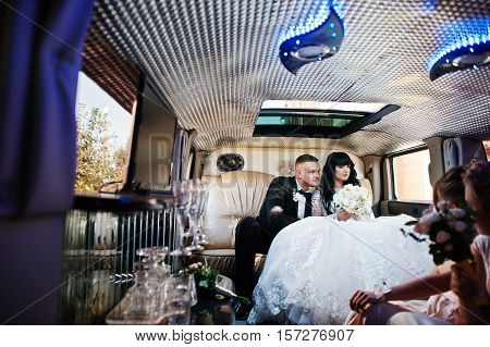 Amazing Wedding Couple Inside Elegance Limousine At Their Awesome Wedding Day.
