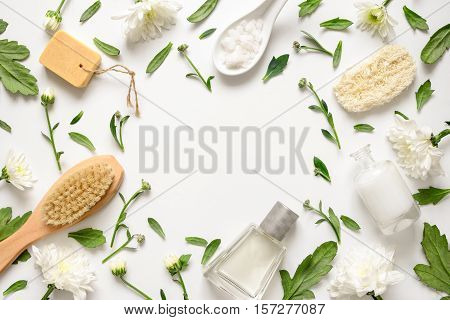 Spa floral background flat lay of various beauty care products decorated with simple white flowers blank space for your text