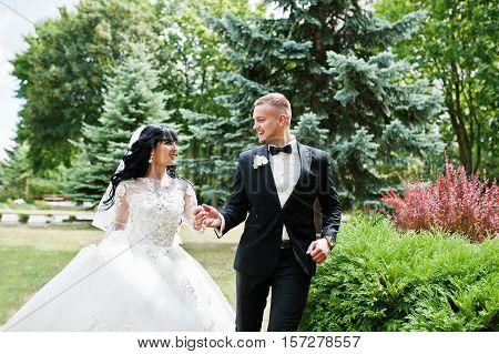 Cheerful Wedding Couple Running Holding Hands On Green Garden Courtyard.