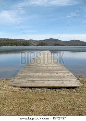 Dock Juts Into Half-Frozen Mountain Lake In Spring