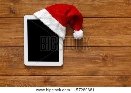 Christmas online shopping background. Tablet screen in santa hat top view on wood with copy space. Electronic devices, internet commerce on winter holidays concept