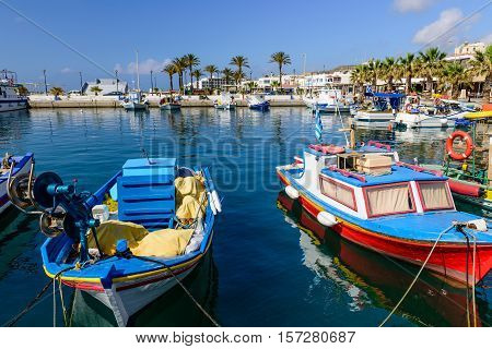 The scenic harbour with traditional fishing boats in the village of Kardamena, Kos island, Dodecanese, Greece.