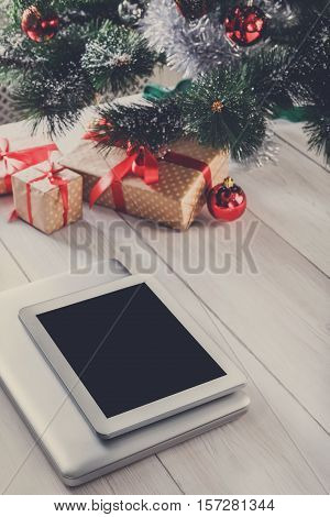 Christmas online shopping. Laptop and tablet with copy space on screen lay on white wood, present boxes under christmas tree on background. Internet commerce on winter holidays concept