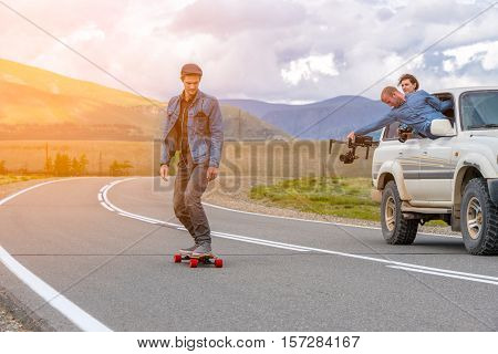 Man rides a longboard in the mountains. Near riding cameraman in SUV car. He takes out the window with an electronic steadycam
