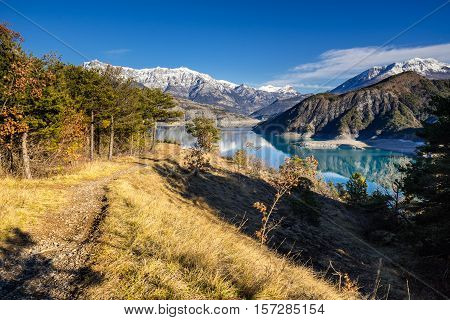 View from hiking trail of Serre Poncon Lake in Winter with snow covered mountains. Le Rousset, Hautes Alpes, Southern French Alps, France