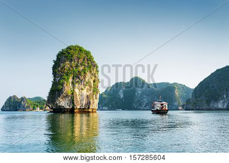 Scenic View Of Rock Pillar And Tourist Boat In The Ha Long Bay