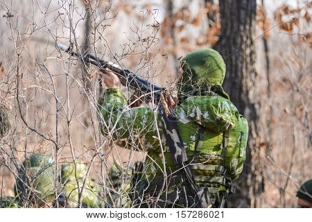 Russian soldiers in camouflage shoots from a Kalashnikov in the woods
