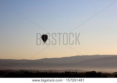 Hot air balloon in the morning twilight over the fields of france