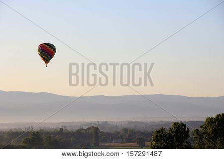 Hot air balloon in the morning mist over the fields of france