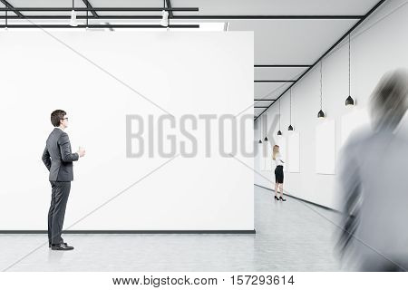 Men and woman are looking at blank posters in an art gallery. Concept of modern art. 3d rendering. Mock up.