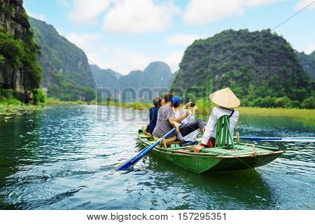 Tourists traveling in boat along the Ngo Dong River and taking picture of the Tam Coc Ninh Binh Vietnam. Rower using her feet to propel oars. Landscape formed by karst towers and rice fields.