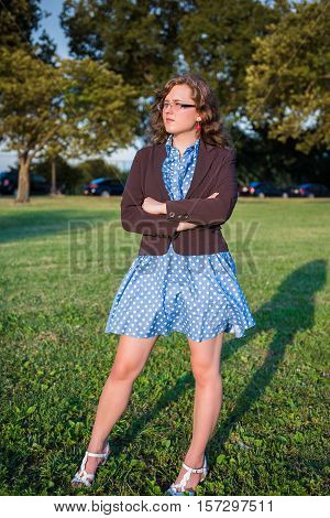 Young woman standing in park with arms crossed in polka dot dress and business jacket