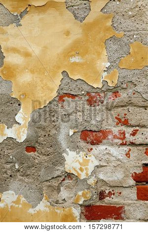 Grunge Brickwall With Broken Stucco Vertical Texture. Old Brick Wall With Damaged Shabby Yellow Plaster  Background. Lime Wash Distressed Stonewall Structure. Chipped Rough Uneven Stone Wall