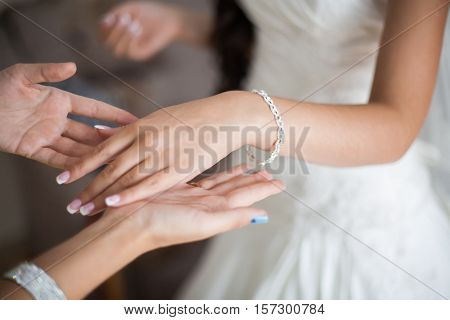 Bride wrapping pearl bracelet on hand, closeup