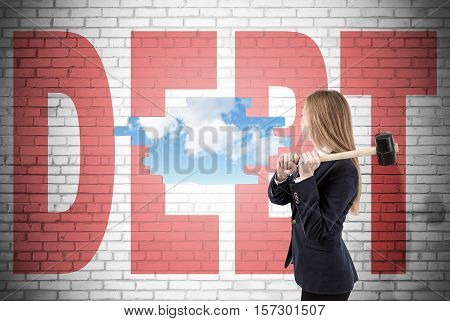 Woman has crashed a white brick wall with sledgehammer and word debt written on it. Sky is seen through the hole. Concept of stabilizing your material situation
